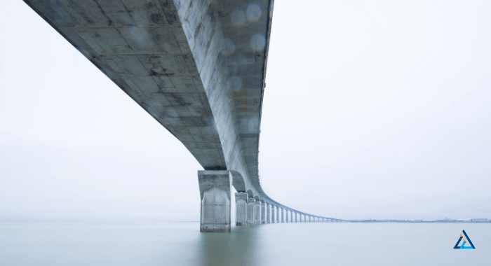 The image shows a bridge over a body of water. The structure is made of concrete and extends into the horizon. The main view of the bridge is its underside, displaying the concrete support pilars and the underside of the road above.