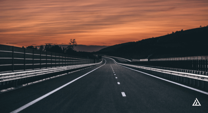 Image of a highway paved with asphalt. The asphalt is new, since it is very black. The road keeps going into the distance against a pink and orange sunset.