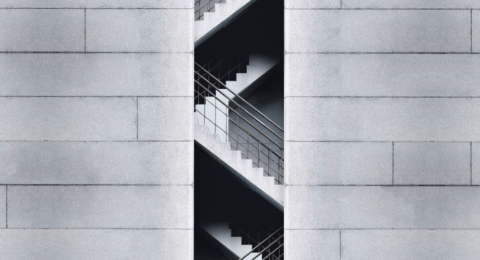 This is the feature image of the blog post Top 3 Reasons to use Air-Entraining Agents in Concrete. The image is a picture of the side of a building, showing its intended architectural feature of exposed concrete. The center of the image shows concrete stairs giving ample acess to the several floors of the building.