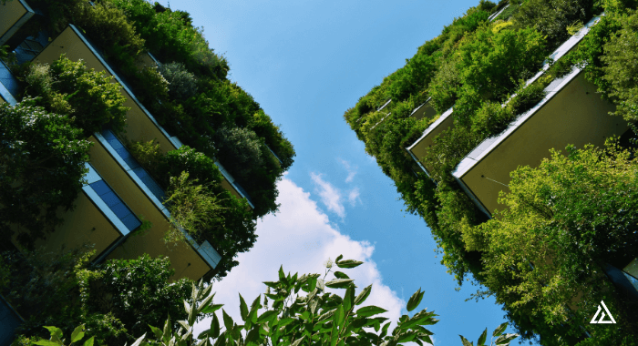 The image shows 2 modern concrete buildings at an angle from the ground up. They are adorned with innumerous plants and greenery. The blue sky is visible between them. On Earth Day, this image represents the progress done so far towards a greener and more sustainable future in the concrete industry. But the challenges continue. There is much to be done to decarbonize the concrete industry as a whole.