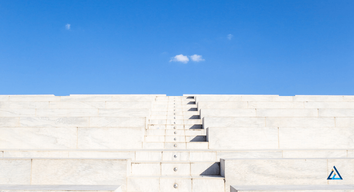 Image is a photo of concrete stairs taken from below. The angle leads the eye to to the top of the stairs. The concrete stairs are light gray and contrast with the clear blue sky on the horizon. The stairs do not look new, but in excelent shape. Most likely air entrained concrete was used to make them last the outdoor conditions.